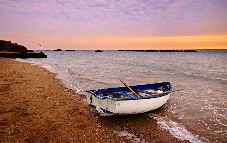 Una barca, sola, in riva  a il mare.