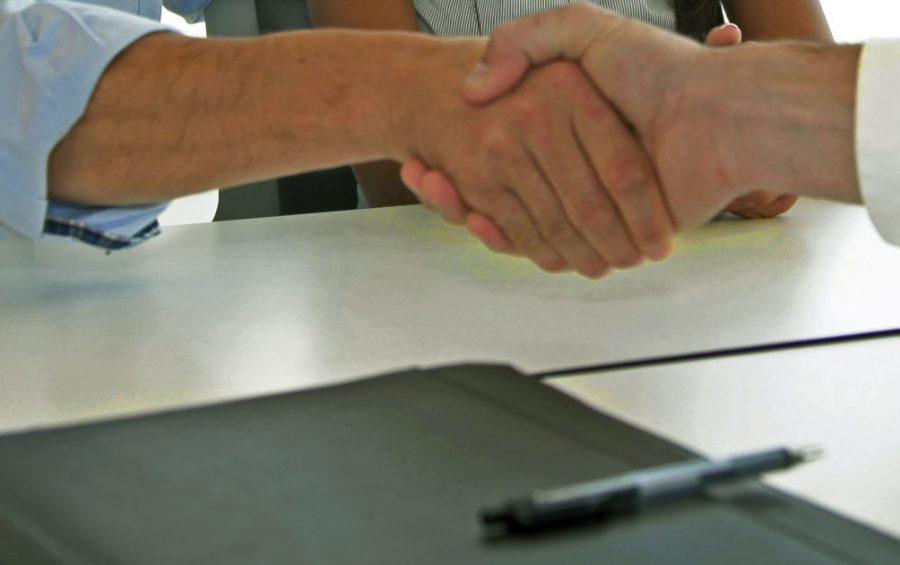 Una coppia prende accordi per un prestito in banca. La stretta di mano.