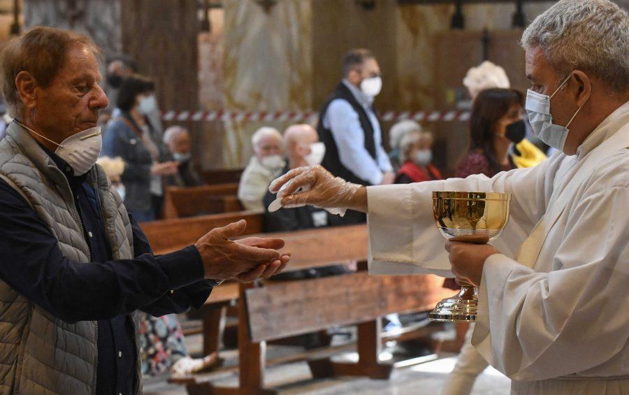 Fedeli al tempo della pandemia del Covid-19, Corona Virus (Coronavirus)  durante la Santa Messa nella Basilica parrocchiale San Giovanni Bosco. Roma, 14 giugno 2020 Eucarestia con guanti e mascherina.